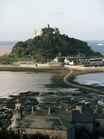 """St Michael's Mount is a tidal isle located 400 yards off the Mount's Bay coast of Cornwall. A civil parish & united w/ the town of Marazion by a man-made causeway of granite setts,passable between mid-tide & low water.Its Cornish language name — literally, """"the grey rock in the wood"""" may represent a folk memory of a time before Mount's Bay was flooded.Remains of trees have been seen at low tides following storms  & radiocarbon dating established the submerging of the hazel wood at about 1700…"""