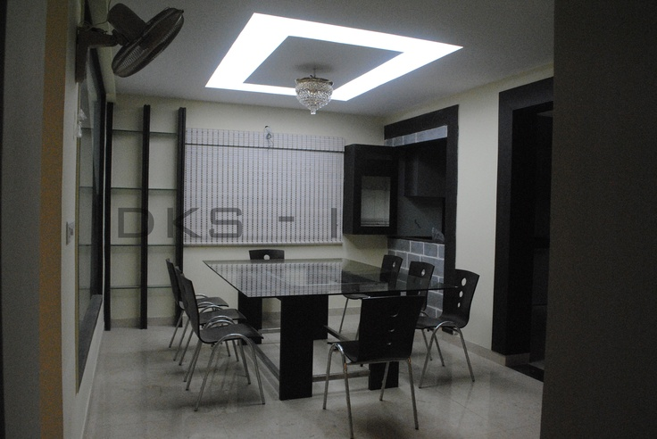 modern glass dining table with sleek SS chairs and false ceiling with lighting make the dining room in to glamor look