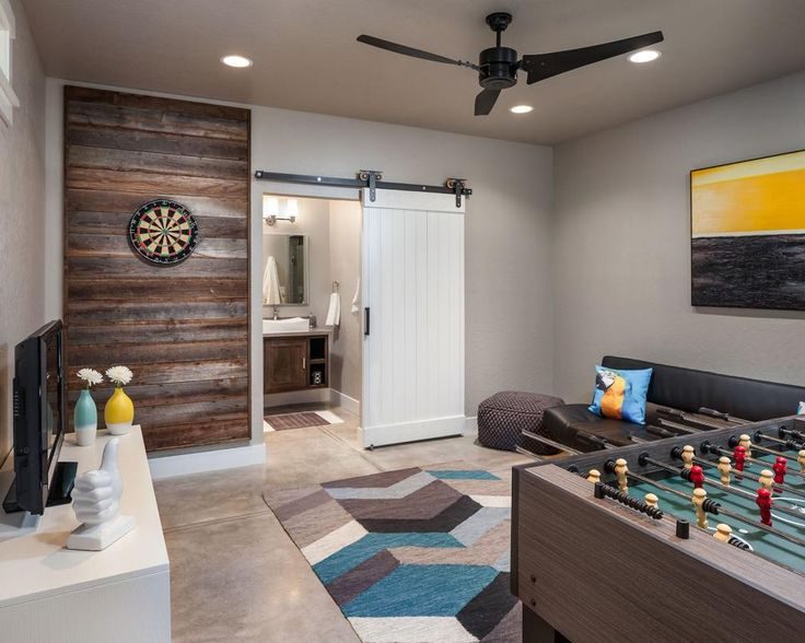 The vibe of this transitional multipurpose room is relaxed and inviting thanks to a blend of contemporary furniture, rustic accents and industrial finishes. A dartboard and foosball table offer fun gaming options, while a TV stands at the ready for movie night. A neutral color palette gives the room an open feel. This room was a winner in HGTV's 2014 Fresh Faces of Design Awards.