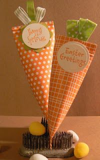 Paper Easter Carrots with Candy - Use Scrapbook Paper Round Paper Punch and Ribbon for Tops -  6×6 Square of Paper -Use Permanent Glue Stick - Roll Paper Over Round Form - Use Tape to Hold Temporarily- Fill with Jelly Beans - Ribbon is held Together with  a Stitch and Then Glued - Punch Holes in Top and Secure with Ribbon - Top Will Then Reseal
