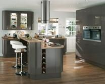 The Glendevon Graphite has a dark grey finish on a high gloss slab door. Extra tall glass wall and curved units complete a contemporary style