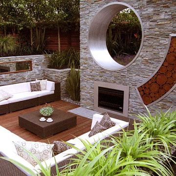 Treat the Fireplace as Sculpture  spectacular fireplace and sunken outdoor living room were designed for the Chelsea Flower Show in England. The massive chimney wall, covered with panels of slate stone, defines the space.