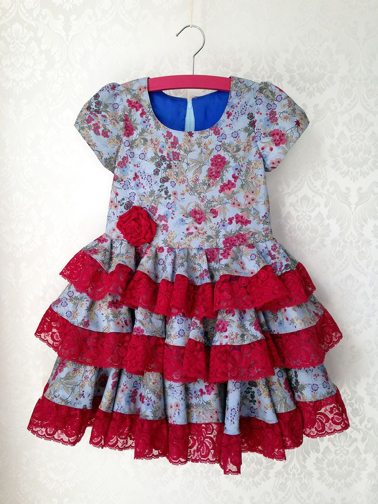 Cute dress with wild flowers and flamenco accents in EU size 122. This dress is suited for girls around the age of 5.
