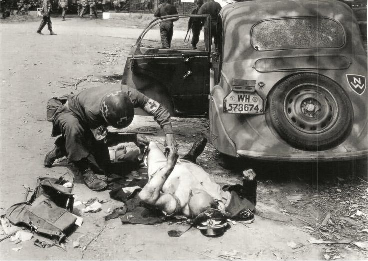 U.S. medic gives treatment to a German officer who has been shot while driving his car, Chartres, France, August 1944