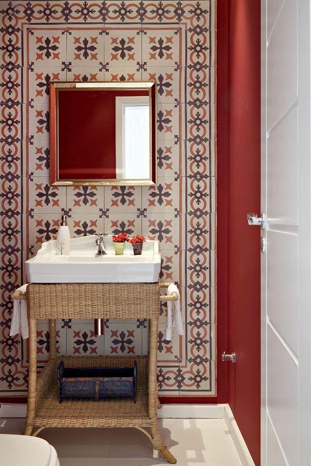 Com liberdade para projetar o lavabo, a designer Andréa Bugarib criou um painel de ladrilhos hidráulicos da Fábrica de Mosaicos, aplicado sobre a parede pintada na cor framboesa.
