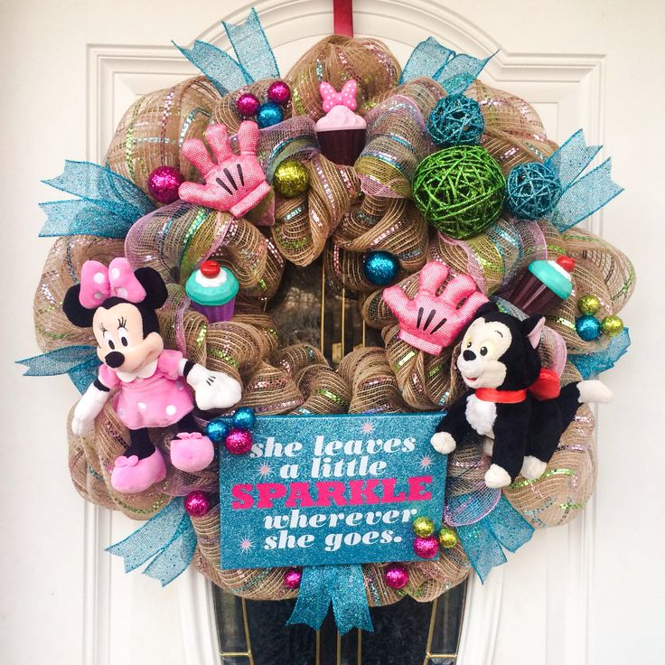 Disney Minnie Mouse and Figaro Cupcake Wreath. This wreath is filled with Minnie gloves from Disney World, custom Mickey head and CUPCAKES!! Minnie Mouse and Figaro are sitting in a burlap like deco mesh wreath with blue, green, pink and purple accents. The cupcakes are accented with Mickey head sprinkles and/or Minnie Mouse's bow. Wreath can be made with any 2 plush of your choice. This is a darling wreath for any princess (or queen)!!