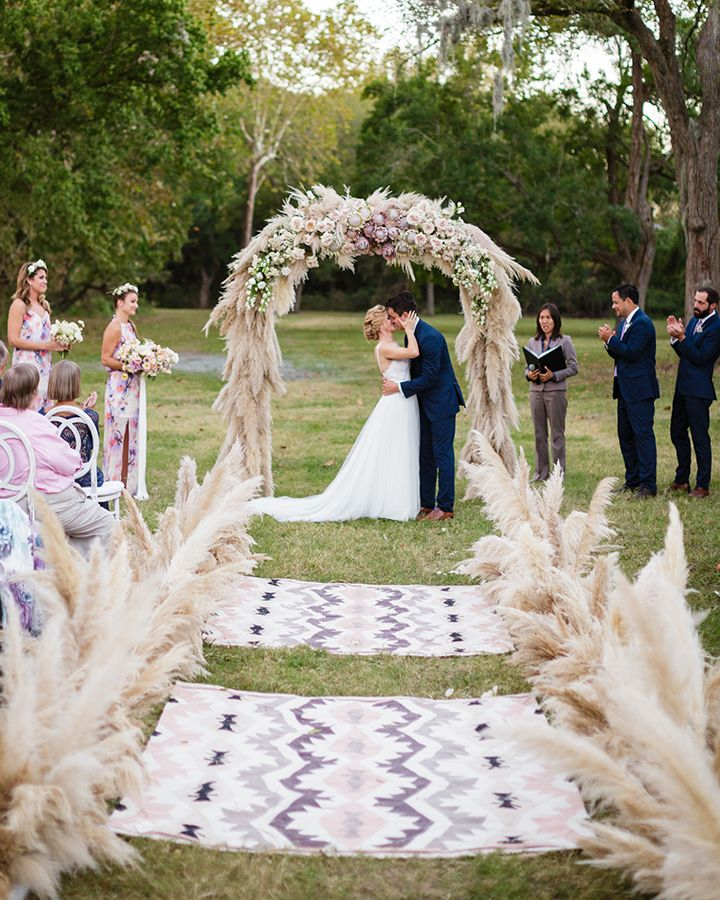 Swooning over Bows + Arrows arch and aisle markers made of pampas grass!