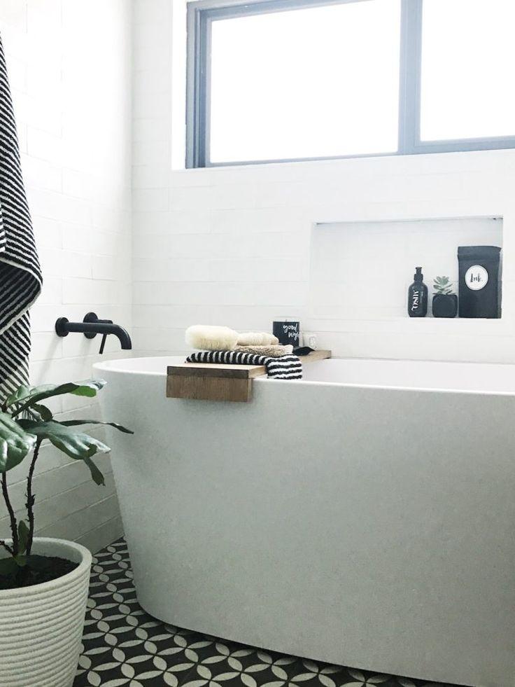Free standing bath tub with DIY bath tray. Black bathroom tapware, black and white petal tile, black and white bathroom accessories. Bathroom niche styling