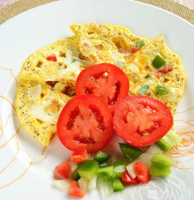 Looking for a savory waffle recipe? Skip the flour and make a waffle omelet! Cook eggs and veggies on a waffle iron for a quick and easy breakfast.