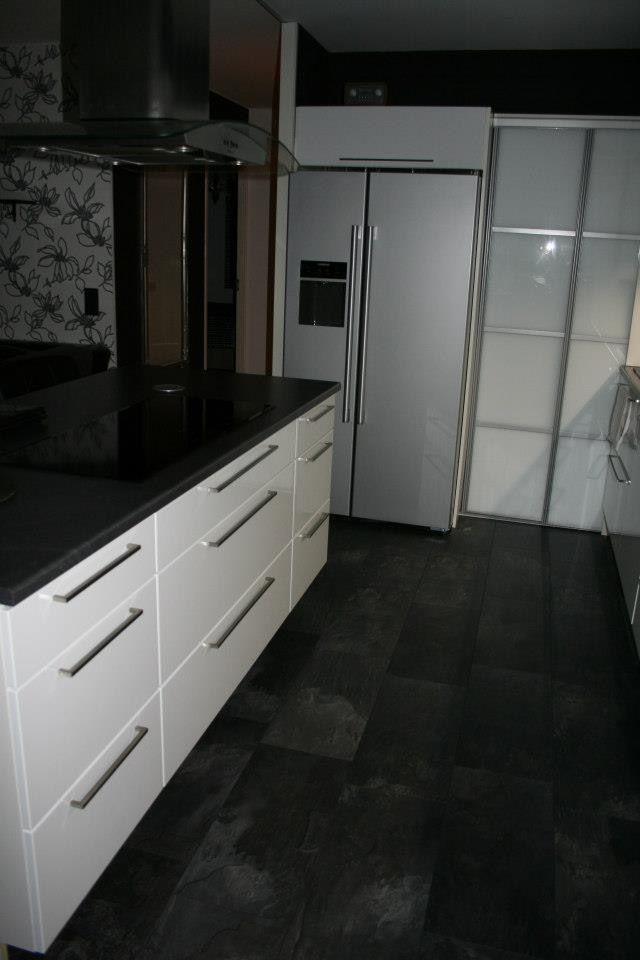 Kerrostaloasunnon keittiön uudistus. Seinä poistettiin olohuoneen ja keittiön välistä, tilalle leveä saareke.