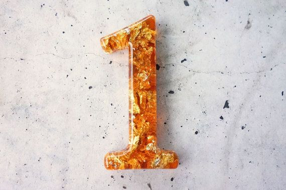 This listing displays a decorative number 1, handmade in Bright Orange coloured resin and detailed with some beautiful faux silver leaf to
