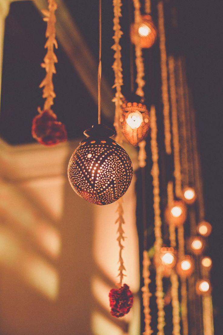 Hanging lanterns & lights - Image by  Chris Spira Photography - A Kerala wedding in India with an ivory and gold bridal sari and bridal party in hues of pink.
