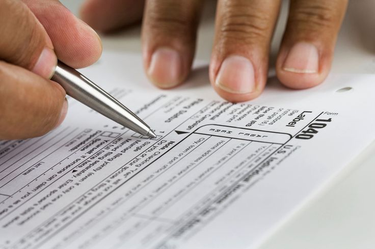 Close up of hands filling in tax form. - Blend Images/Getty Images