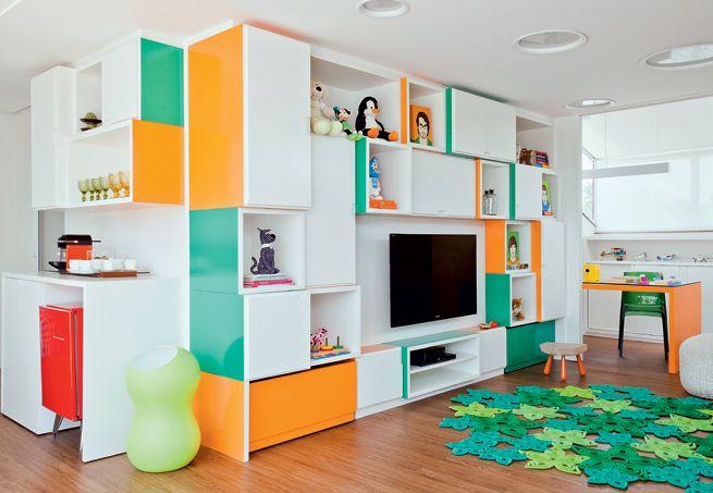 O home theater é a sala de lazer das crianças no projeto de Madá Campos. A estante colorida, composta de módulos desnivelados, agrada também aos adultos. Na base, há gavetões que organizam os brinquedos dos pequenos. O móvel se desdobra em uma bancada de trabalho para os pais