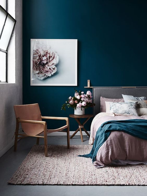 a combo of a navy statement wall and blush textiles and a blush flower artwork looks very refined