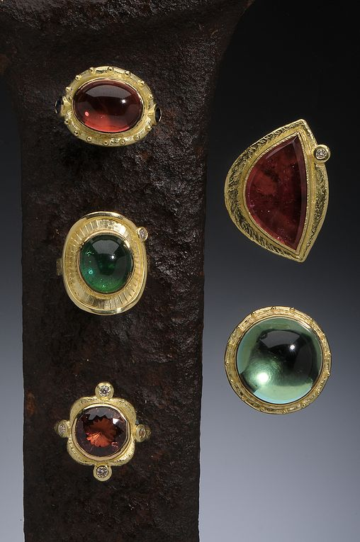 Assorted 18K Rings, clockwise: Antiquity Setting Ring with Salmon Tourmaline and Blue Sapphires; Rubellite Tourmaline Slab; High Dome Green Quartz Cabochon; Salmon Tourmaline with White Diamonds; Green Tourmaline and White Diamond Shield Ring Hughes-Bosca Jewelry | Rings