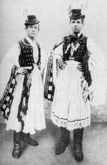 Legények bő ujjú ingeben és ráncba szedett rojtos gatyában 1895-ből. Fejükön darutollas kalap