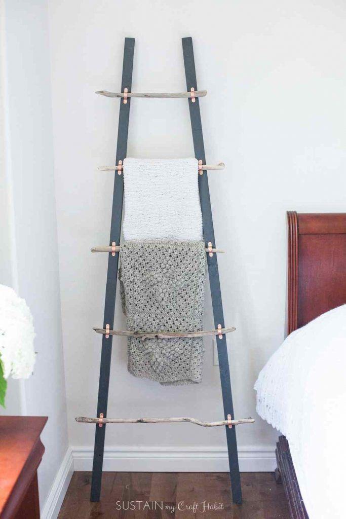 Une échelle porte vêtements dont les barreaux sont en bois flotté fixés par des colliers en cuivre de fixation de tuyau