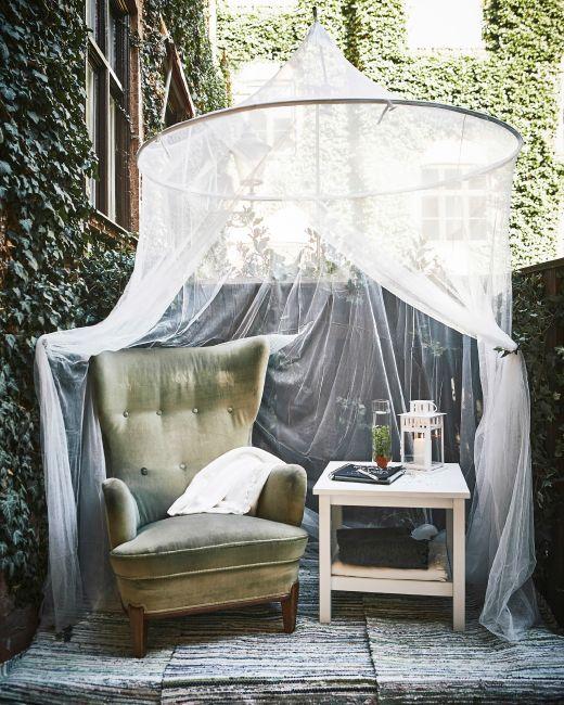 Coin tranquille aménagé à l'écart avec un fauteuil, une table d'appoint et une moustiquaire.