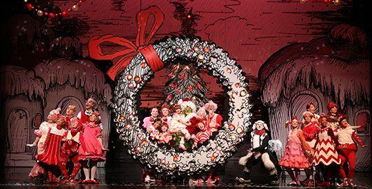 The Grinch cast standing near a wreath