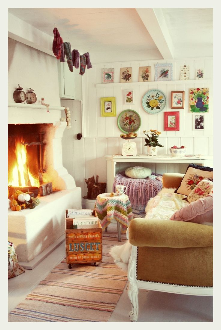 Cosy bohemian living space. Kitsch wall art, open fire place, lovely nanna blanket. So inviting!