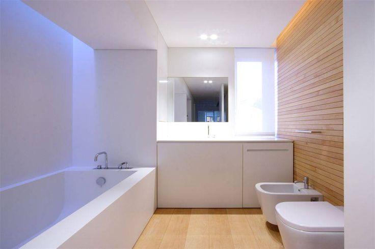 Piccolo bagno bianco con un parete e pavimento in legno chiaro - Start Preventivi