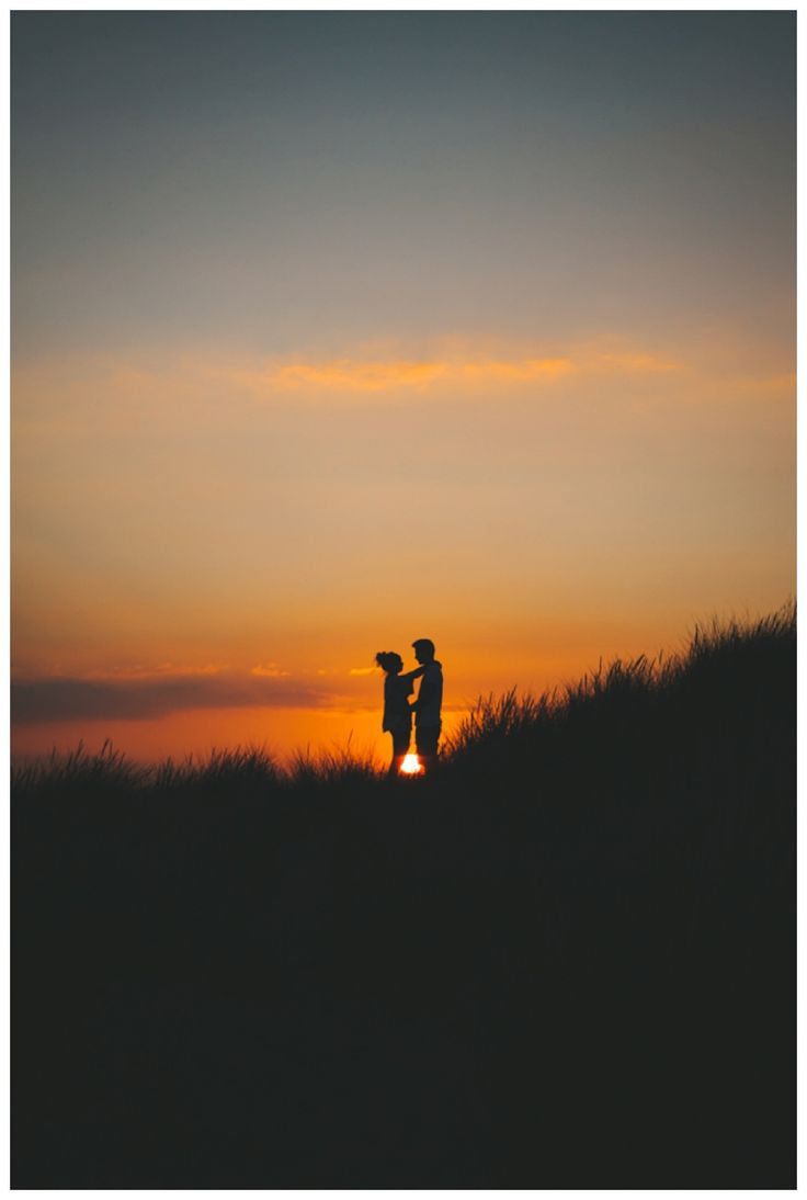 Silhouette of couple at sunset on a hill. www.ellen-richardson-weddings.com/blog