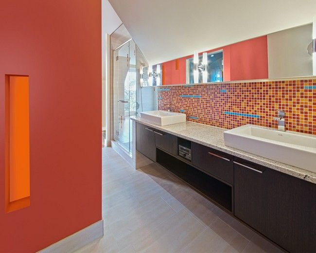 Large rectangular mirror covering upper section of wall, with lower section covered in tile with diverse color palette