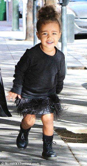 So much energy: The trendy tot wore a feathered skirt, sweater and boots