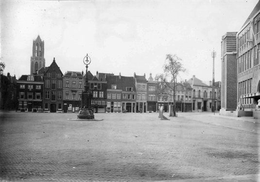 Gezicht op de voorzijde van de huizen aan de zuidzijde van de Neude te Utrecht; geheel rechts een gedeelte van de voorgevel van het Hoofdpostkantoor (Neude 11) anno 1930