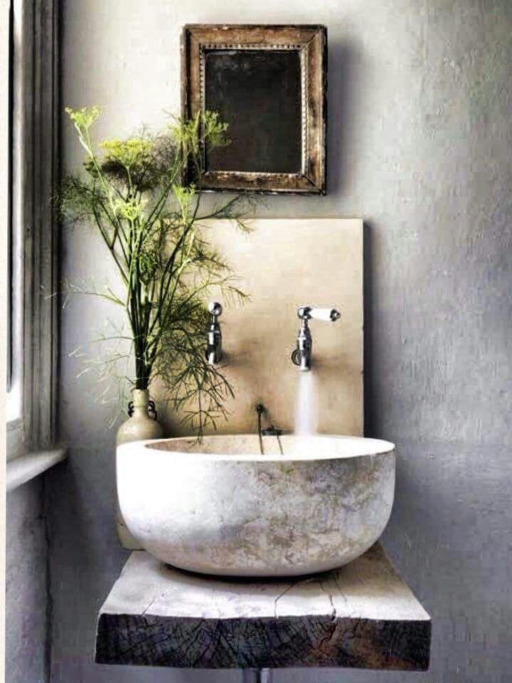 Rustikales von der Natur inspiriertes Badezimmer mit Tageslicht. Schöne Steinerne Wasschüssel auf naturbelassenem Holz Brett. Antike Amaturen und grüne Pflanzendeko fürs Bad. Schlicht und minimalistisch und trotzdem ein echtes Highlight.