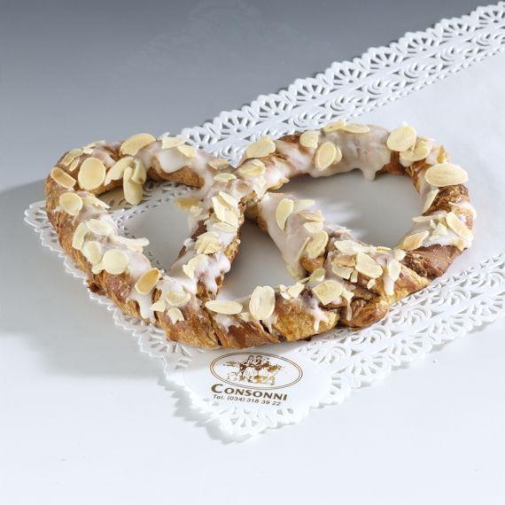 Precel Przygotowana z ciasta półfrancuskiego i czekolady drożdżówka uformowana w kształcie precla. Obsypana prażonymi płatkami migdałowymi.