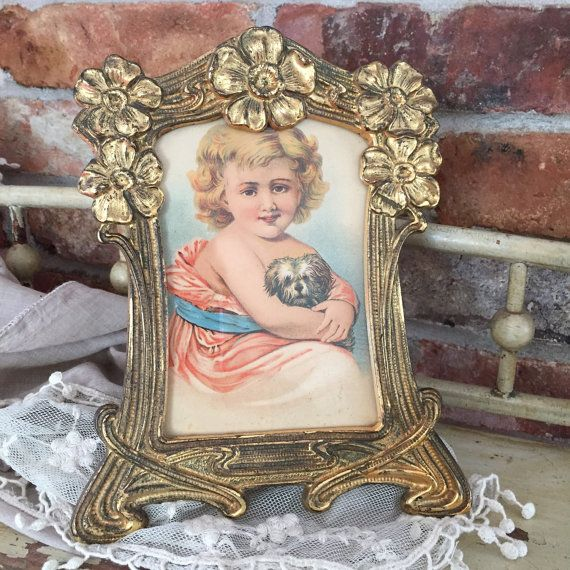 Oh what an adorable child and dog in this wonderful colored lithograph . It is all set in a gold wash tone authentic Art Nouveau period cast metal frame. The frame is decorated in style with the traditional flowers and vines. The frame has its own stand in back and screw holders to keep the picture tightly in place. It has a glass front. The gold is worn but adds to its antiquity and romance. This is from an old New Hampshire Estate and fresh to the market. I have not removed the backing to…