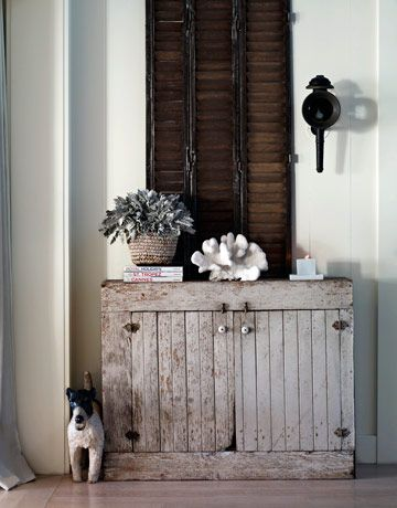 Love this gorgeous distressed cabinet w/ the coral on top. Also liking the dark shutters behind it.