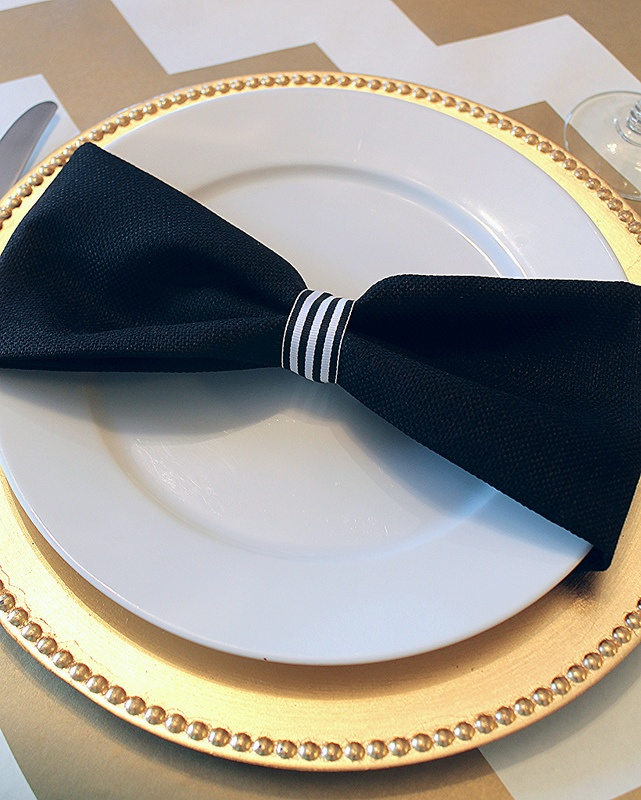 Tablescape- Contemporary yet Classic styling includes gilded charger, unadorned china plate, navy bow-tie napkin with mini-stripe ribbon holder, on a tan and white chevron linen tablecloth. -MMA