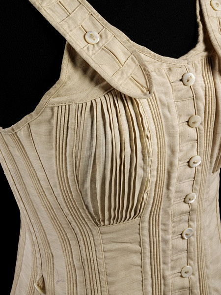 1890  Girl's corset made of unbleached cream wool. Made in two halves joined at the centre back and at the front with mother-of-pearl buttons attached to very long cotton threads. It reaches from the shoulder where there are adjustable woollen shoulder straps to the hip. It is boned at the centre front and back, but the bands of stiffening  is achieved with inserted cords and tapes. It is only slightly shaped at the hip and waist but there are narrow pleated gussets for the breasts