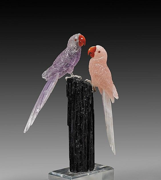<b>LARGE AMETHYST AND ROSE QUARTZ MACAW PAIR</b> <br  /> <i>Artist: Peter Müller</i> <br  /> These beautiful birds were superbly carved by master lapidarist Peter Müller in his studio in Brazil, from finest local rose quartz and amethyst. Each displays superb detail to their plumage, with agate eyes and beaks and sterling silvered feet, perched on a large, deep green-black tourmaline crystal column, in a perspex display base, 13 3/4 inches high overall.