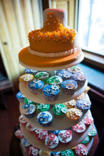 Gele bruidstaart met bonte gekleurde cupcakes op etagere