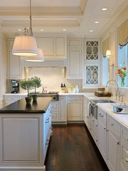 narrow island with dark wood, grey counters, white cabinets