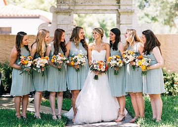 spring bride and bridesmaids in pale mint green dresses. cream, peach, pale green and blues and pops of orange highlight the bouquets.