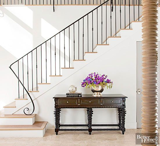 Striking in its simplicity, an iron stair railing captivates attention thanks to its kicky newel post and linear design. Straight balusters embellished with knucklelike details partner with a slim rounded handrail to guide eyes and traffic upward without disrupting the home's peaceful rhythms.