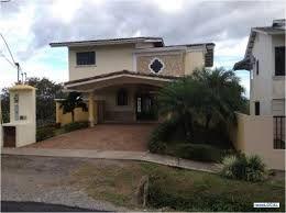 El punto focal de esta casa es el rosetón prefabricado sobre el techo de la cochera...la palmera a la derecha representa la única belleza de la fachada