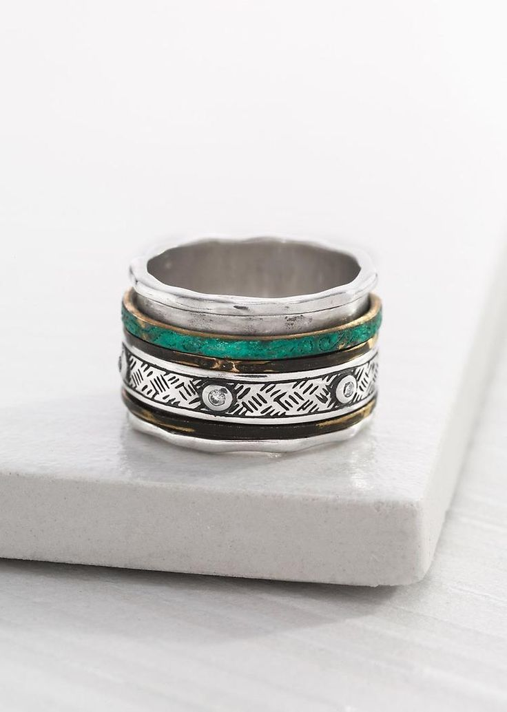 Isabella Spinner Ring 6240 Bands of Patina Brass and Sterling Silver come together to form a dynamic design. Material: Brass, Sterling Silver