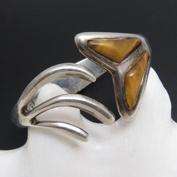 Solid, heavy and well made vintage sterling clamper bracelet with a unique fishtail design set with tiger eye stone. Opposite side has swirled tail. Distinctive and unusual vintage sterling bracelet. Marks or signatures: TM-M2 (I think - the two Ms are kind of cut off), Mexico 925 Measurements/size: 50 grams; 1 3/8 inch at widest part Condition: Very good - very minimal signs of wear from normal use - could use cleaning if you wish Find lots more vintage jewelry at Purple Daisy Jew...