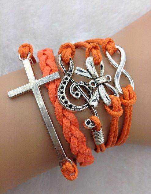 Pulsera color naranja dijes de infinito,moño, clave de sol, y cruz