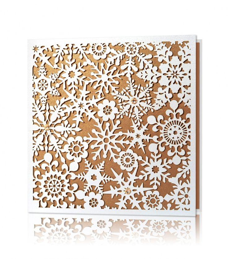 Biały oraz miedziany perłowy papier, laserowe wycięcie. Kartka świąteczna utworzona z laserowych motywów śnieżynek, umieszczonych na miedzianym tle wkładki. Całość dopełniają ręcznie naklejane kryształki w kolorze złoto-miedzianym.