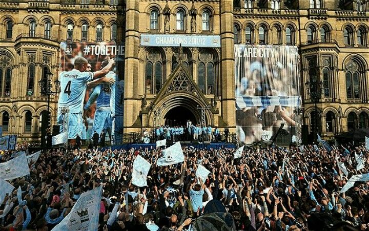 Manchester City fans celebrate at Manchester Town Hall after winning the Premier League.