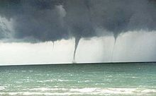 A waterspout is an intense columnar vortex (usually appearing as a funnel-shaped cloud) that occurs over a body of water. They are connected to a towering cumuliform cloud or a cumulonimbus cloud. In the common form, it is a non-supercell tornado over water. - Wikipedia, the free encyclopedia