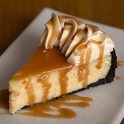 Rich & decadent White Chocolate Cheesecake, drenched with salted caramel sauce on a chocolate cookie crust.