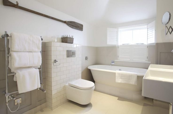 contemporary country neutral palette bathroom with heated towel rail, freestanding tub and shutters  | Luxury small hotel by the sea in St Ives, Cornwall - thetidehouse.co.uk